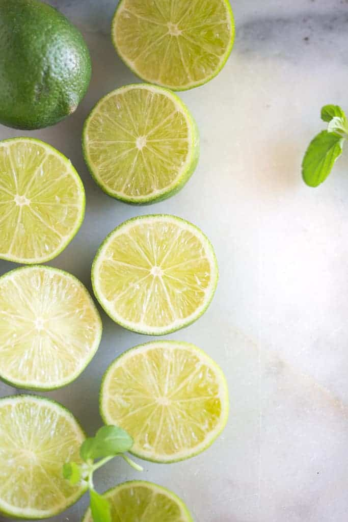 An overhead photo of sliced limes lined along a white marble board.