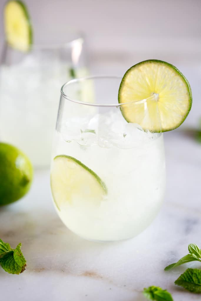 Two glasses with ice and fresh limeade, a slice of lime in the cup and a slice of lime resting on the edge.