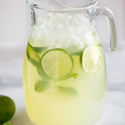 A clear glass pitcher filled with mint limeade, ice, slices of fresh lime and springs of fresh mint, ready to serve.