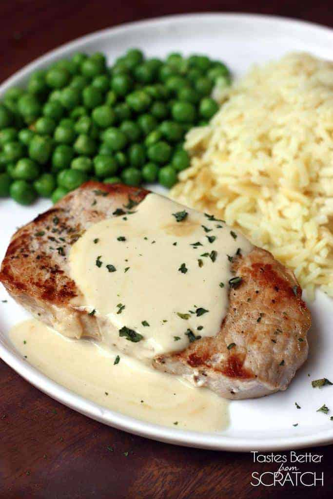 Pork chops with creamy mustard sauce tastes better from scratch a dinner plate with a cooked pork chop covered in creamy mustard sauce and peas and ccuart Choice Image