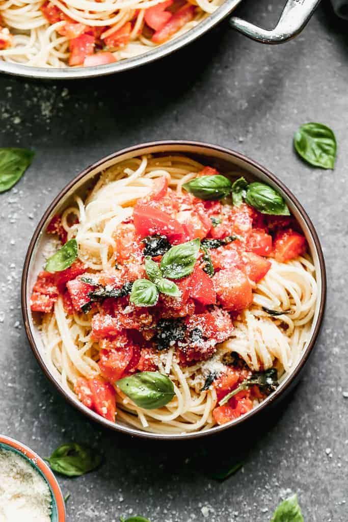 A bowl with cooked spaghetti topped with a fresh tomato basil sauce.