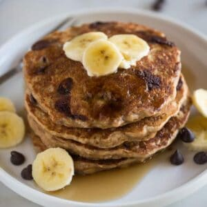 A stack of whole wheat banana bread pancakes on a white plate topped with sliced bananas with chocolate chips on the plate and in the background.