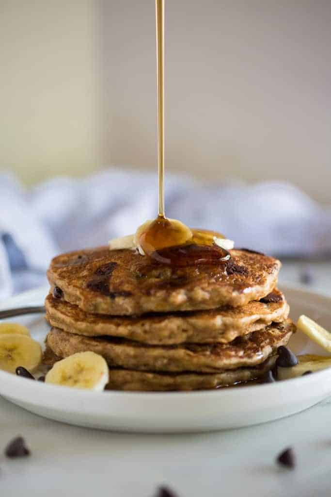A line of syrup drizzled onto a stack of whole wheat banana bread pancakes.
