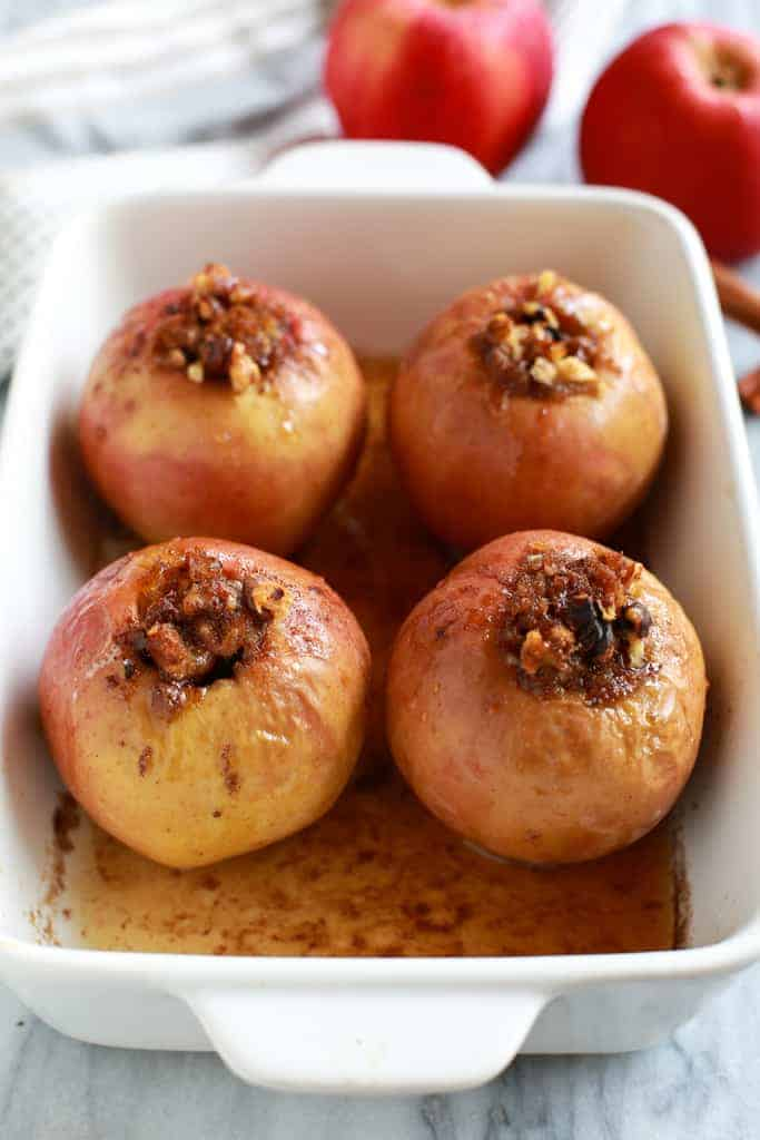 Four baked apples filled with a cinnamon sugar mixture, baked in a white casserole dish.