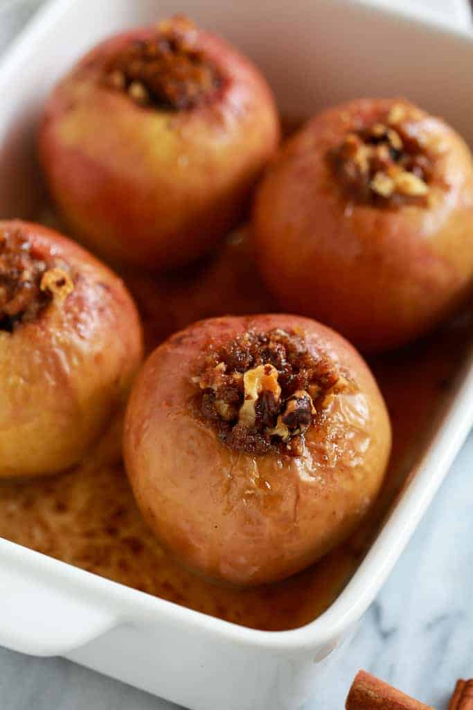 A pan full of four baked apples.