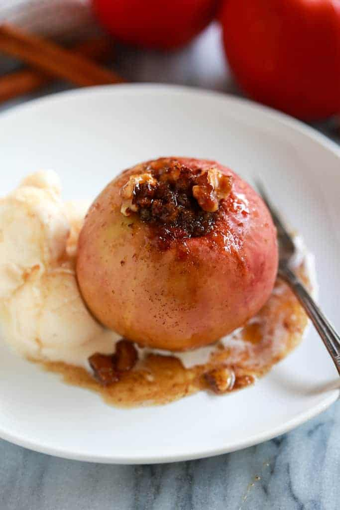 Baked apple on a white plate with a fork and a scoop of vanilla ice cream.