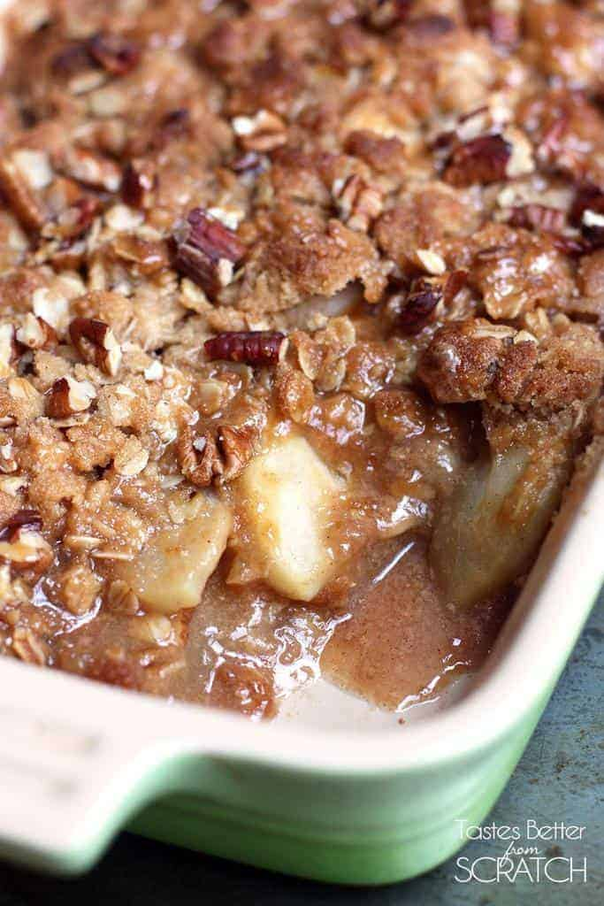 Caramel Pecan Apple Crisp in a casserole dish with a spoonful taken out.