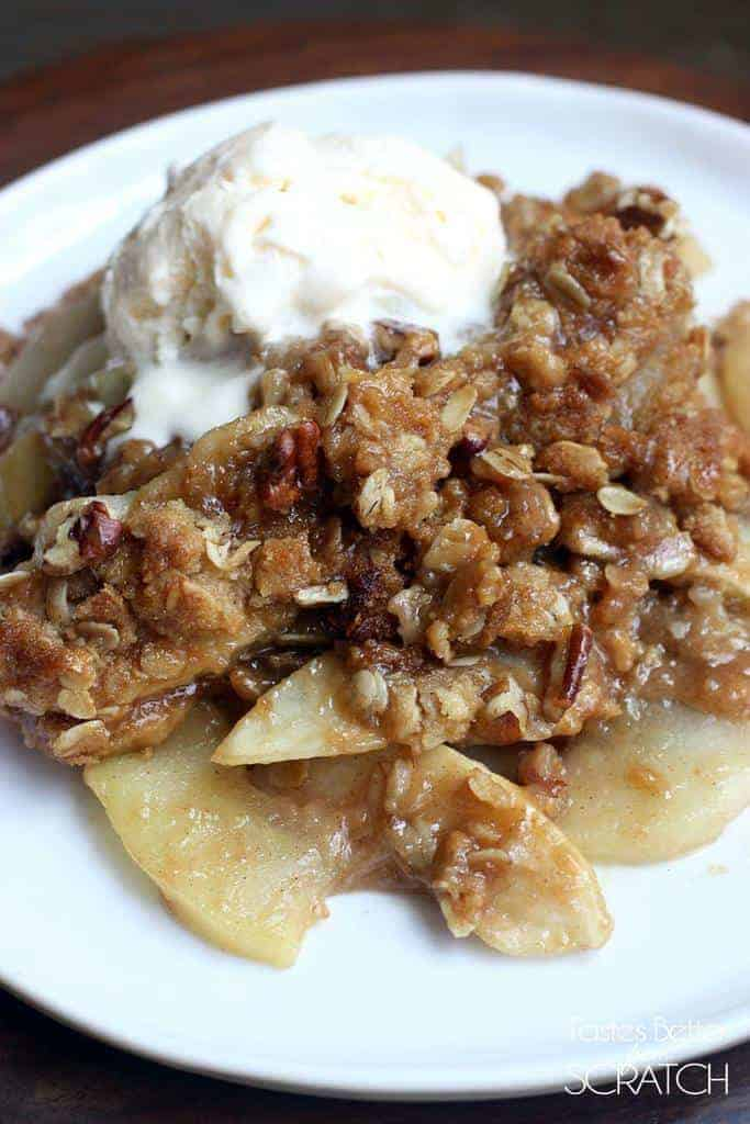 Apples topped with a pecan crumble and a scoop of ice cream.