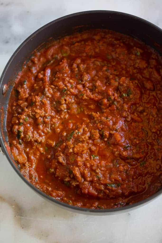 Overhead photo of a saucepan filled with homemade spaghetti sauce.