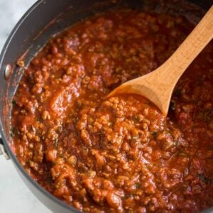 Homemade spaghetti sauce in a saucepan with a wooden spoon.