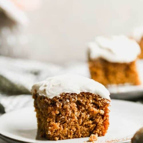 A slice of pumpkin cake with cream cheese frosting, on a plate.