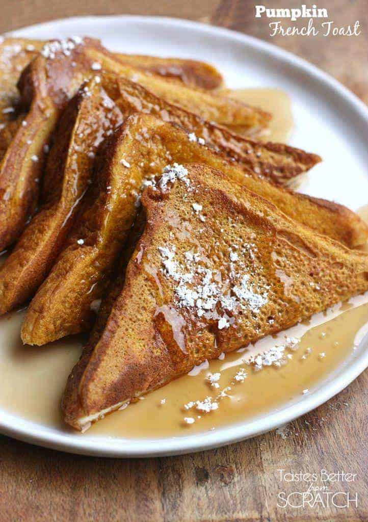A circular plate loaded with five slices of pumpkin french toast with sprinkles powdered sugar and syrup on top.