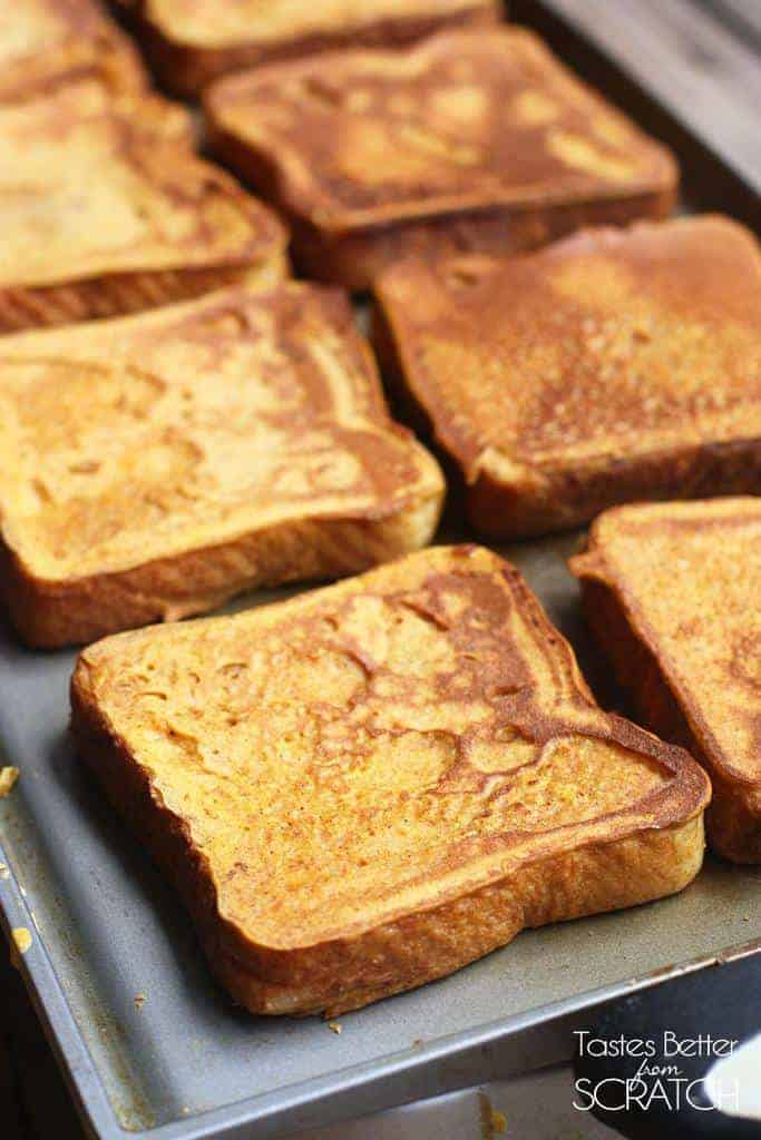 A griddle cooking 8 slices of pumpkin french toast.