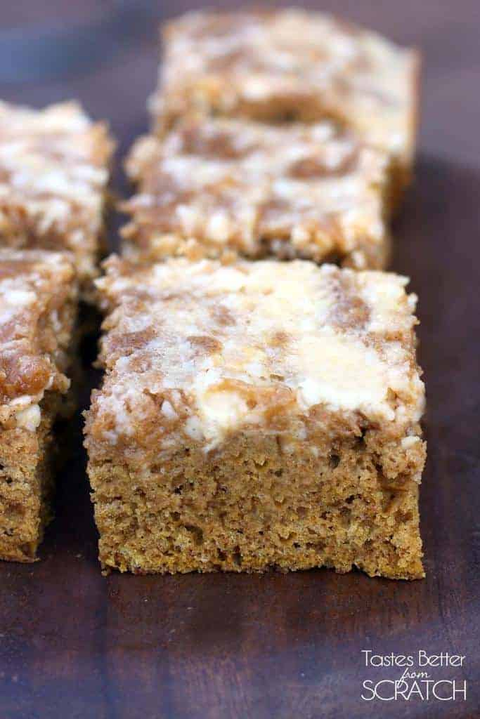 Several slices of Pumpkin Roll Cake on a wood tabletop, covered in cream cheese frosting.