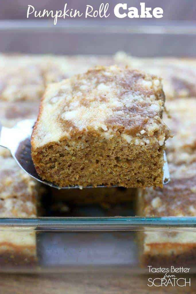 A close up of a slice of pumpkin roll cake with cream cheese frosting being lifted out of the pan by a spatula.