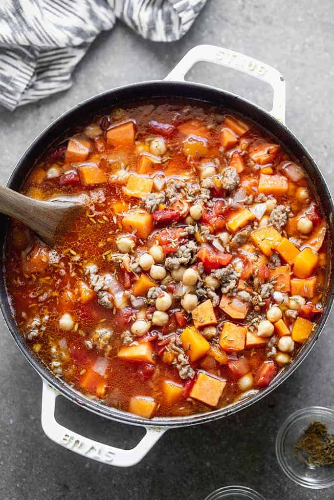 Overhead photo of a large cast iron soup pot filled with butternut squash and sweet potato soup with sausage, diced tomatoes and a wooden spoon.
