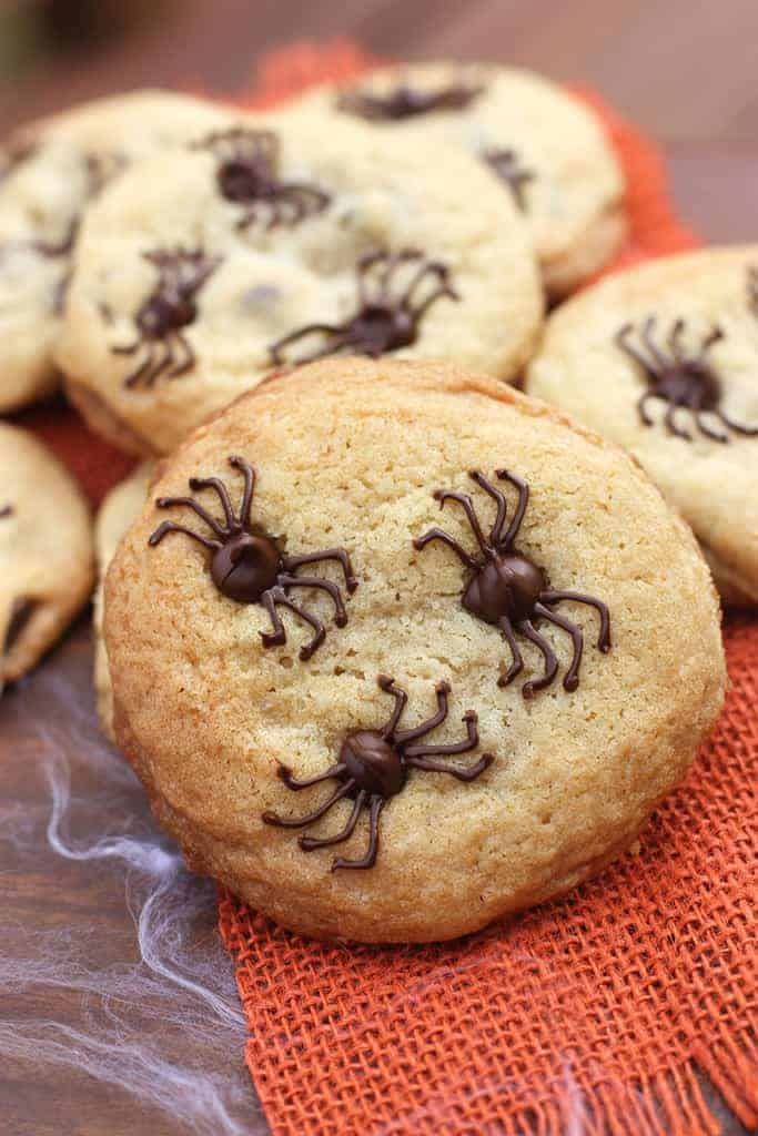 A few cookies on a wooden table with chocolate chips in each and the chocolate chips are each frosted to look like Halloween spiders.