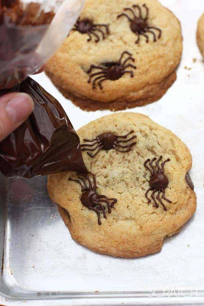 Chocolate chip cookies on a cookie sheet with a person using a plastic bag of melted chocolate to frost spider legs onto the chocolate chips.