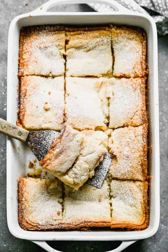 A 9x13 pan of baked gooey butter cake with a spatula removing a piece.