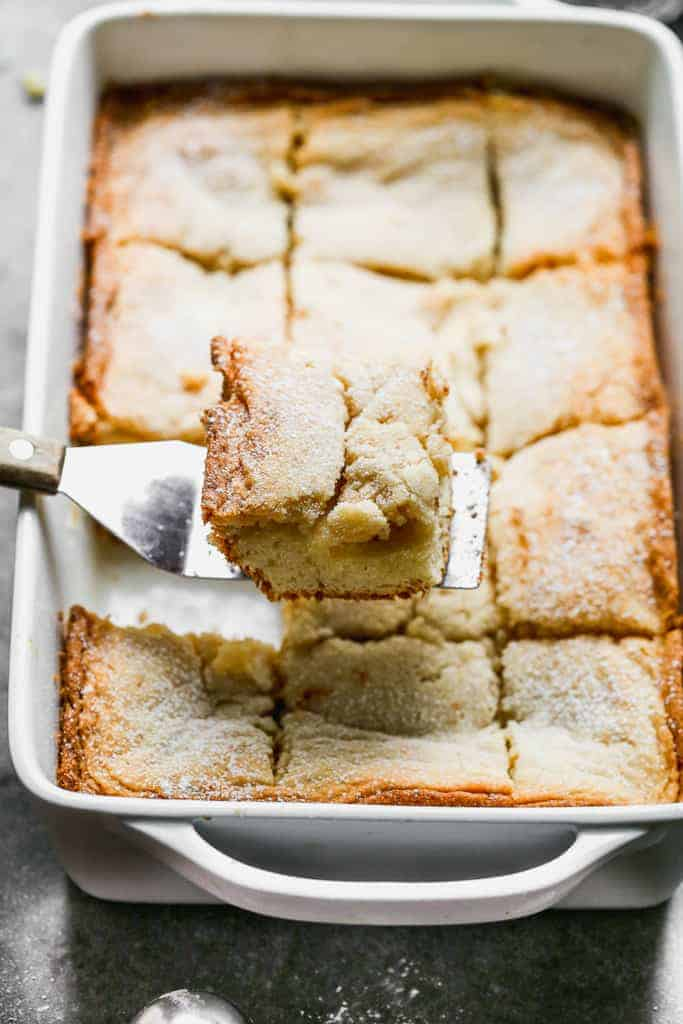 A spatula removing a slice of homemade gooey butter cake from a white 9x13 pan.