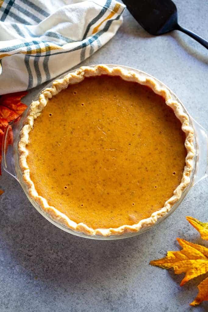A baked pumpkin pie with dish towel, fall leaves and serving spatula on the side.