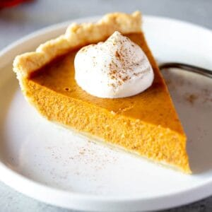 Pumpkin Pie slice with whipped cream on top, on a a plate.