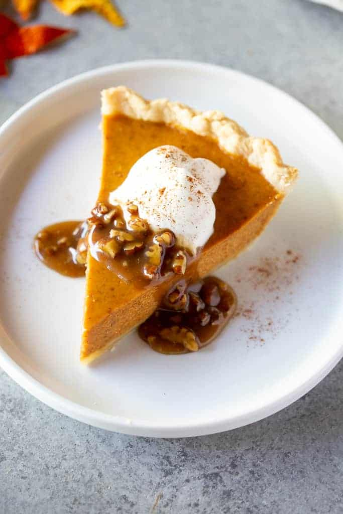 Slice of pumpkin pie with caramel pecan sauce and whipped cream on top.