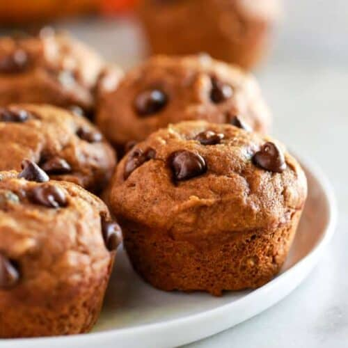 Healthy pumpkin muffins with chocolate chips, on a white plate.