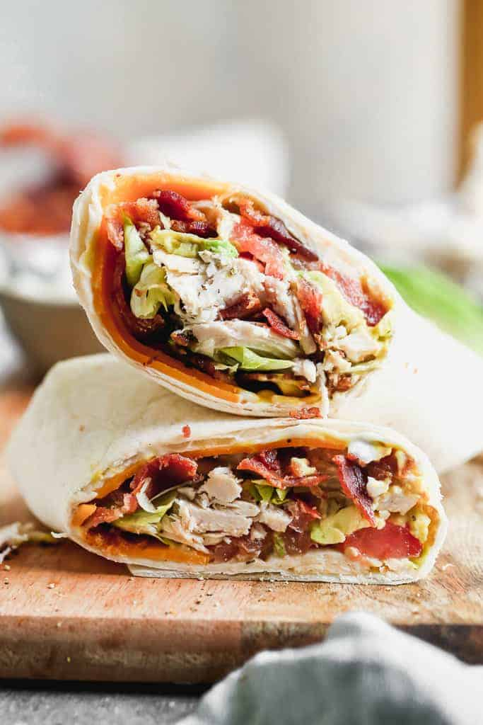 A turkey wrap in a flour tortilla, cut in half, served in a wooden board.