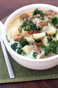 White bowl filled with creamy zuppa toscana soup with chunks of potato, browned italian sausage, bacon and chopped kale, sitting on a place mat, next to a spoon.