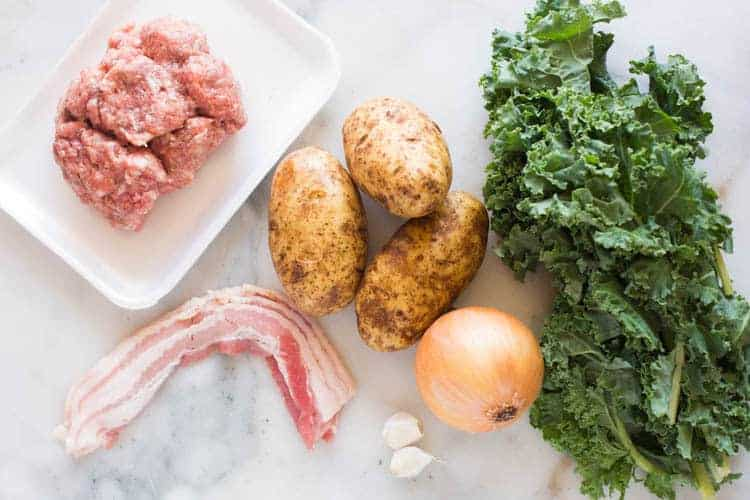 Ingredients for zuppa toscana soup, including italian sausage, russet potatoes, bacon, onion, garlic and kale.