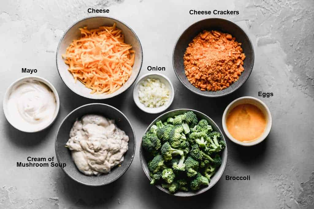 Individual bowls with the ingredients needed to make broccoli casserole and text overlay of the ingredient names.