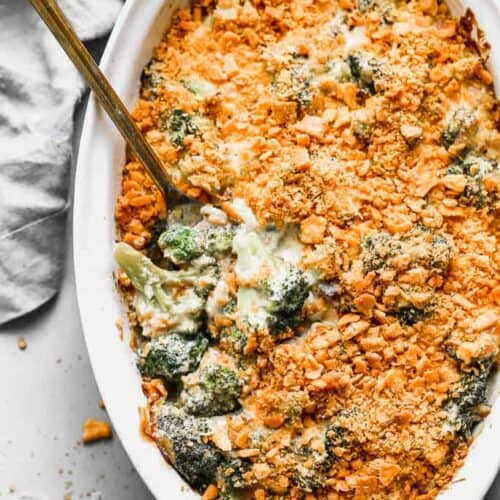 Broccoli Casserole baked in an oval serving dish with a spoon in it, for serving.