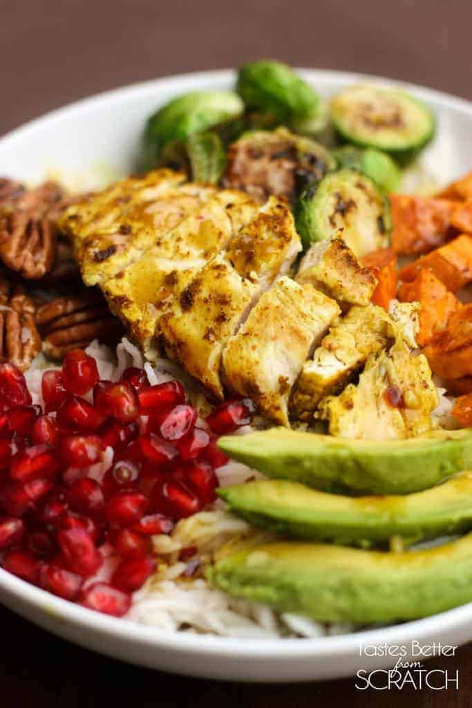 A Coconut rice rice bowl topped with roasted butternut squash and brussels sprouts as well as pecans, avocado, and pomegranate.