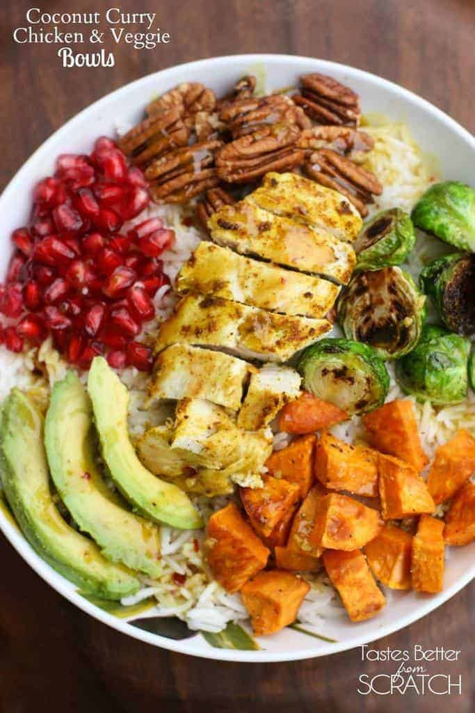 A white bowl filled with coconut rice topped with pomegranates, avocado, curry chicken, pecans, butternut squash, and roasted brussels sprouts.