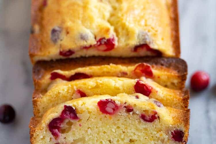 A loaf of Cranberry Orange Bread with three slices cut from it.
