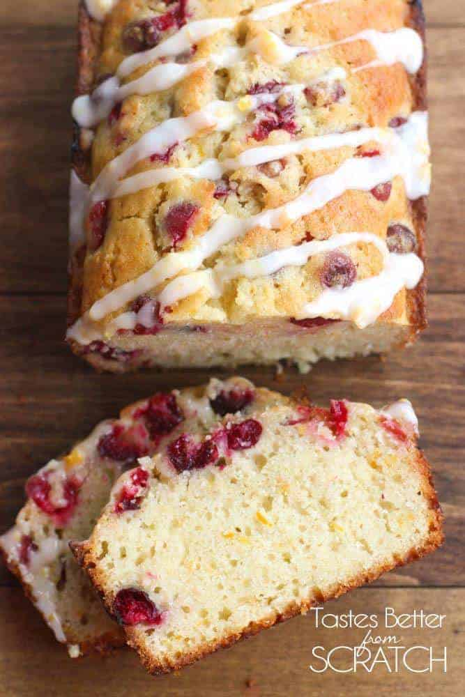 An overhead view of Cranberry Orange Bread with two slices cut off and topped with a sweet orange glaze.