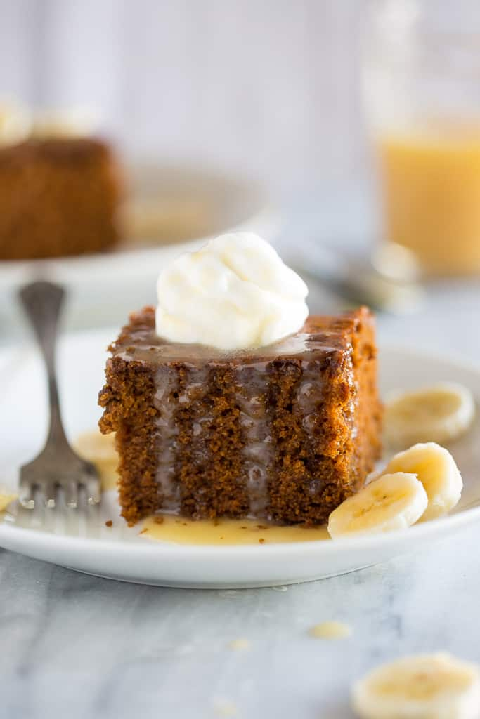 Gingerbread cake served on a white plate with a dollop of whipped cream on top, sliced bananas on the side and a vanilla cream sauce on top.