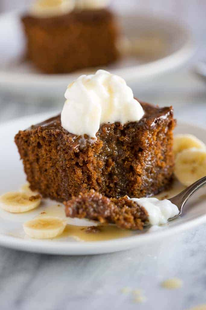 Gingerbread cake with a bite taken out of it, served on a plate with sliced bananas and vanilla cream sauce.