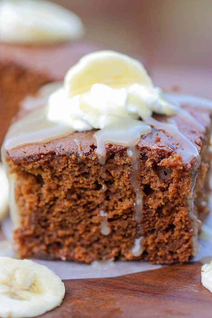 One slice of Gingerbread Cake topped with Vanilla Cream Sauce, a dollop of whipped cream and a banana slice.
