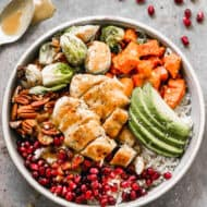 Harvest Bowls served over coconut rice, in a bowl, and topped with chicken and veggies.