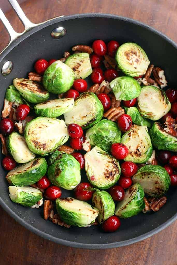 A roasting pan filled with halved brussels sprouts, whole fresh cranberries, and pecans.