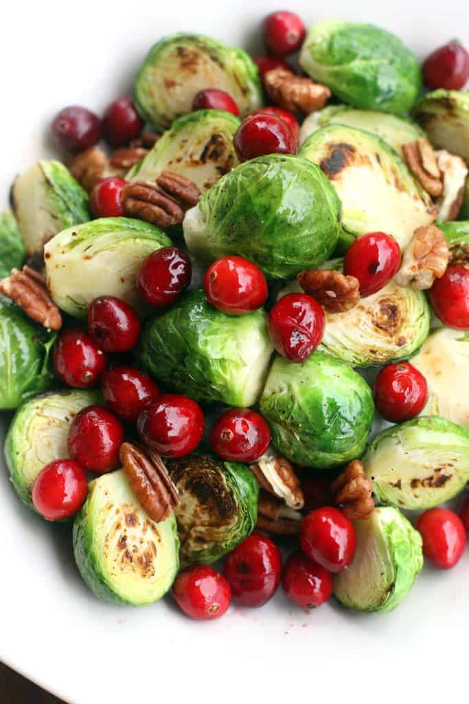 An overhead shot of cooked brussels spouts with cooked cranberries and pecans.