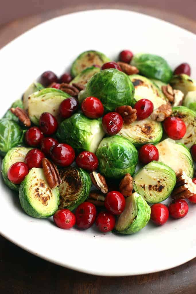 A white plate filled with halved and sauteed brussels sprouts, cranberries, and pecans.