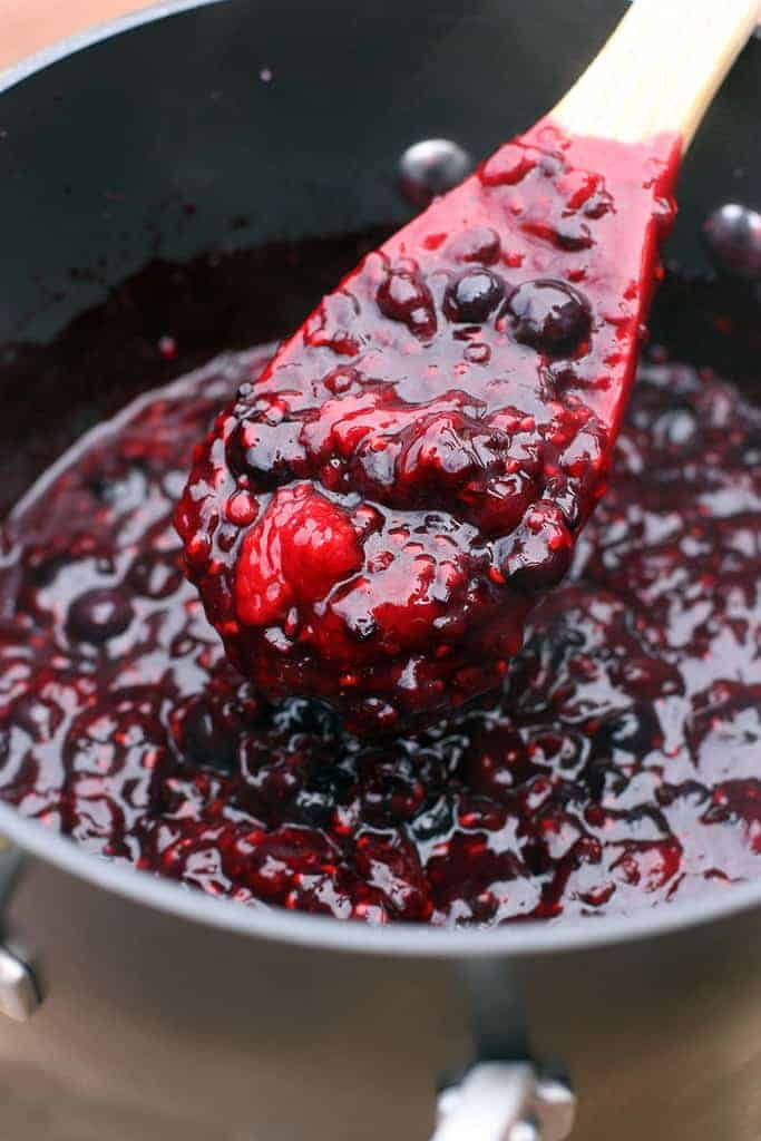 A saucepan full of homemade berry pie filling with a wooden spoon in it.