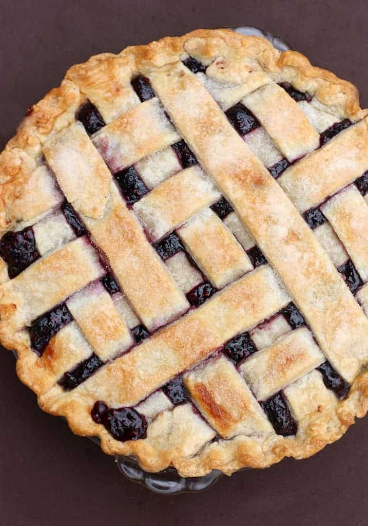 An overhead shot of a triple berry pie with a lattice crust.