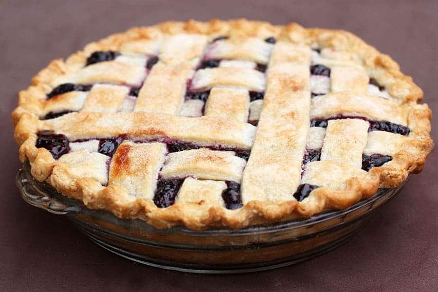 A large triple berry pie with a lattice crust in a clear glass pie tin.