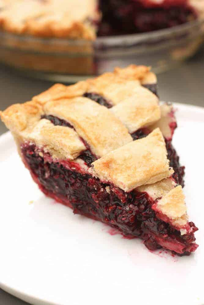 One slice of triple berry pie on a white plate with a lattice crust and the rest of the pie in the background.