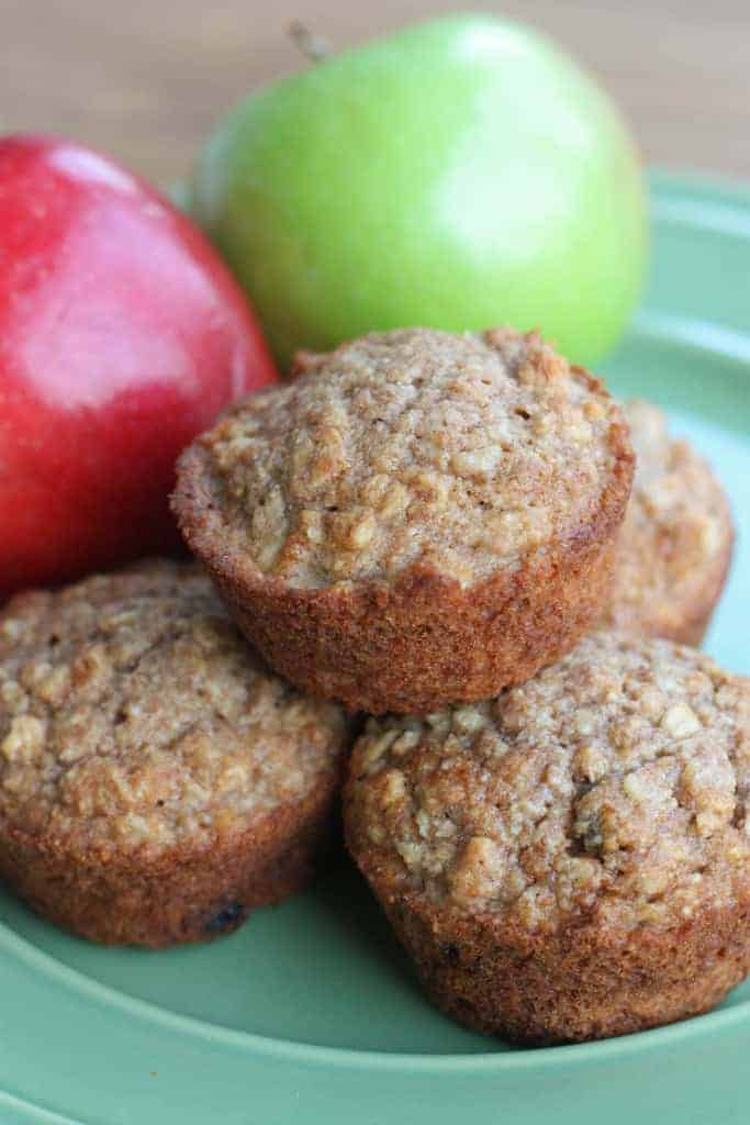 A plate with three applesauce oat muffins and one muffin stacked on top with two apples in the background.