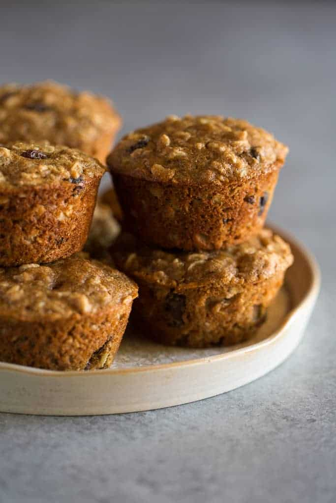 Healthy applesauce oat muffins stacked on a plate.
